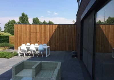 Tuinhuis in verlengde van carport- afwerking thermowood multilatten. 2 deuren, 1 schuifdeur softclose, 2 ramen- dakafwerking EPDM