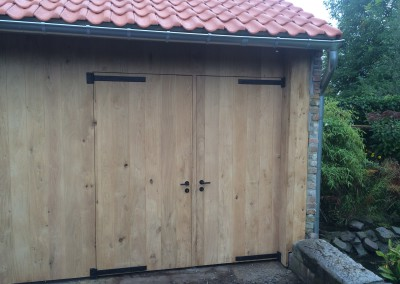 Vernieuwing eiken bijgebouw- pannen dak- Europese eiken bekleding en dubbele poort in zwart stalen scharnieren